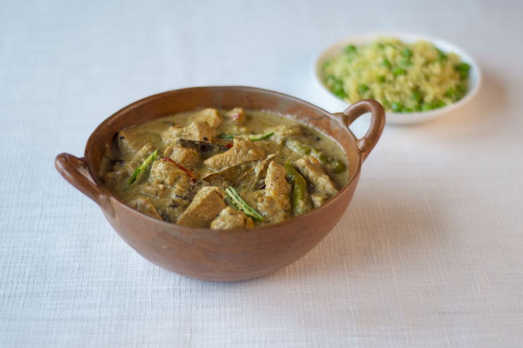 Picture of a bowl of Chicken Korma and a plate of pilau rice with peas.