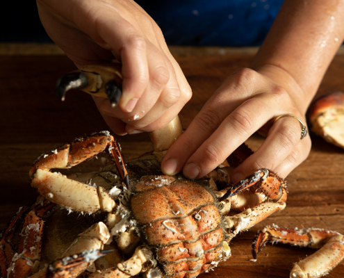 Twisting the legs off a cooked crab